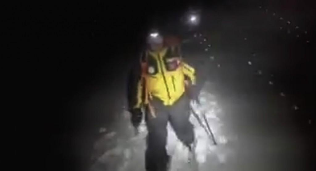 I Finanzieri Alpini nella tormenta di notte sugli sci mentre vanno verso l'Hotel