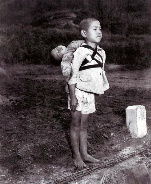 bambino di Nagasaki con il fratellino morto sulle spalle mentre aspetta per la cremazione