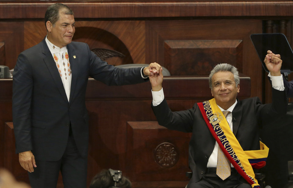 Incoming President Lenin Moreno, wearing the Ecuadorian presidential sash, raises his hand with outgoing President Rafael Correa, during the swearing-in ceremony, in Quito, Ecuador, Wednesday, May 24, 2017. Moreno was sworn into office Wednesday after narrowly defeating a conservative former banker in last month's runoff. (AP Photo/Dolores Ochoa)