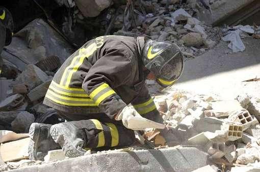 un pompiere scava nelle macerie